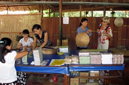 Travelers visiting coconut candy workshop in Ben Tre