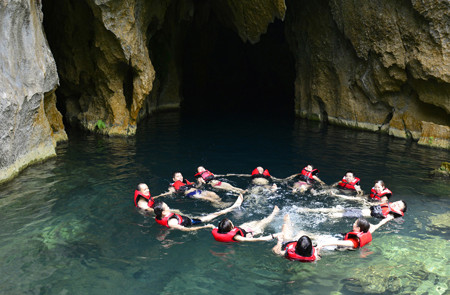 Swimming in the crystal clear water of E cave (Trung Tre cave)