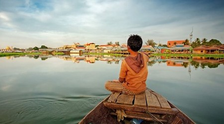 A young Cambodian boy on a boat approaching a floating village on the Tonle Sap in Siem Reap, Cambodia.