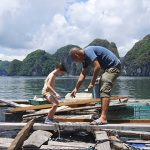 cua van floating village with children in halong bay